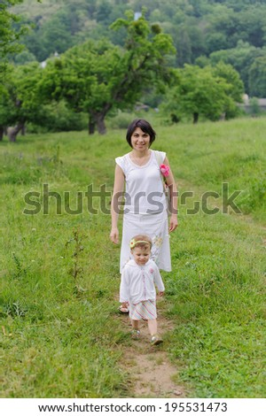 mother walking with her daughter in meadow - stock photo