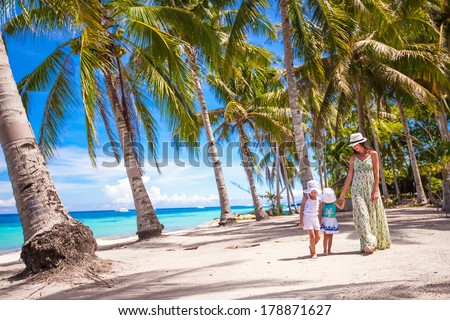 Mother walking with her two kids in the palm grove - stock photo
