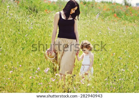 mother walking with toddler girl in green field - stock photo