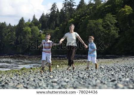 mother walking with two boys on a beach - stock photo