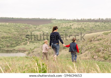 Mother walking with two small boys in the countryside holding their hands as they stride across a grassy hilltop on rolling hills above a river valley - stock photo