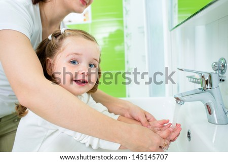 mother washing kid hands - stock photo