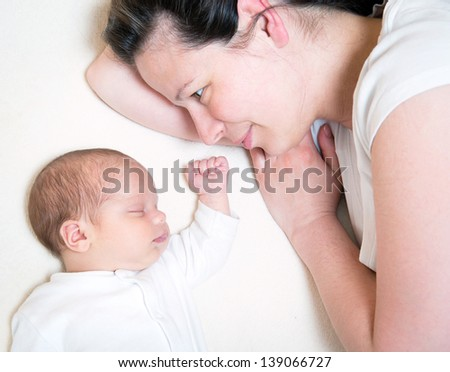 mother watching her month old son sleeping - stock photo