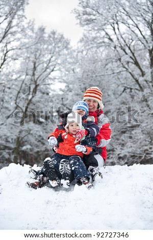 Mother whit children Sitting On A Sled In The Snow - stock photo
