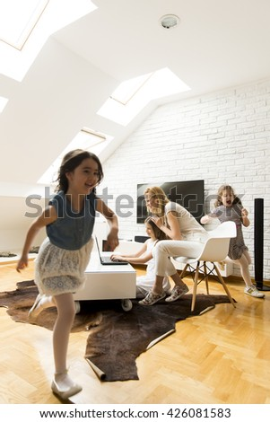 Mother with a daughter on the laptop while other girls playing - stock photo