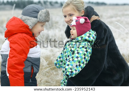 mother with a small child winter outdoors - stock photo