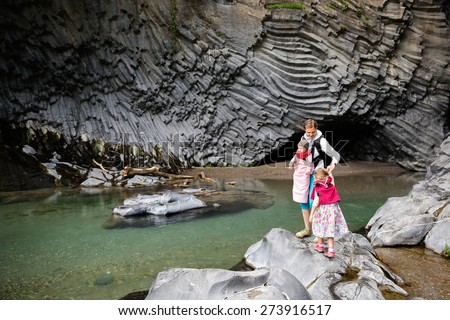 Mother with baby and little girl on an adventurous hiking trip through geologically interesting river gorge Golle del Alcantara in the foothills of Mt. Etna, Sicily, Italy. Family travel concept.  - stock photo