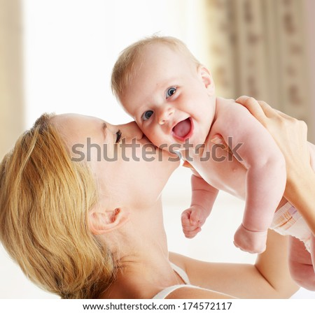 Mother with baby at home. Happy family with newborn indoors - stock photo