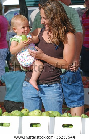 Mother with baby daughter picking out pears to buy at a farmer's market. - stock photo