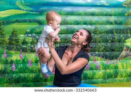 Mother with baby doing gymnastics. Fun mood. - stock photo