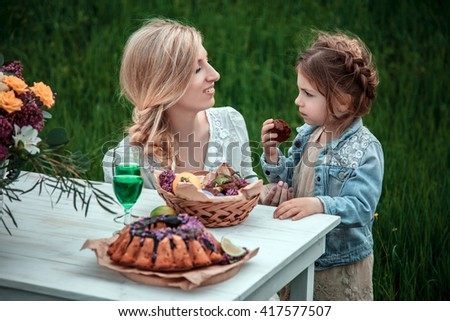 Mother with baby on picnic. Little girl eats chocolate cake. The concept of life values, peace, security and love - stock photo