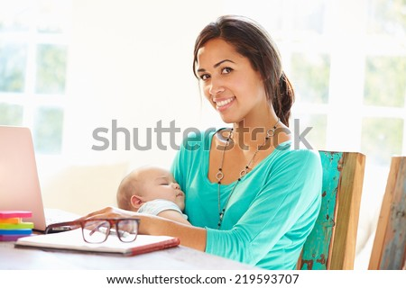 Mother With Baby Working In Office At Home - stock photo