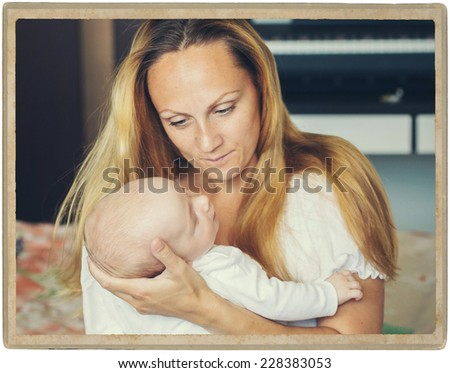 mother with child baby infant at home in room on bed vintage card - stock photo