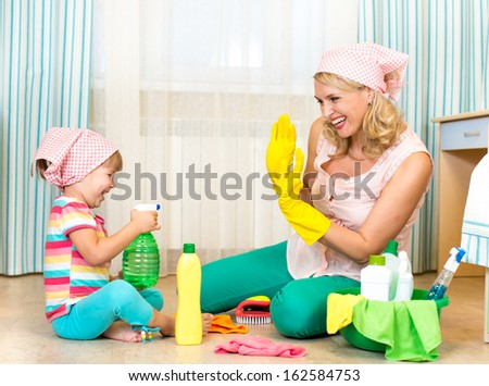 mother with child cleaning room and having fun - stock photo