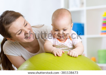 Mother with child doing exercises with green gymnastic ball at home. Concept of caring for the baby's health. - stock photo