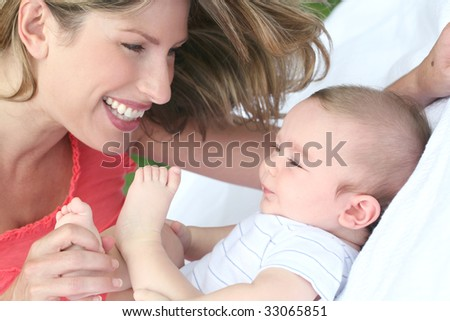 Mother with child (infant baby boy son), smiling and happy - stock photo