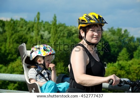 Mother with child sitting  in a bike seat enjoy views on the River Danube. They have a helmet because of safety. - stock photo