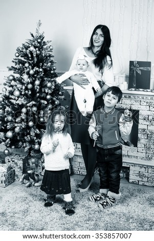 Mother with children on christmas holiday at home. Happy family concept - stock photo