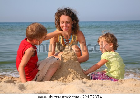 mother with children playing with sand on beach - stock photo
