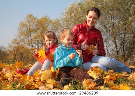 Mother with children sit on fallen maple leaves - stock photo
