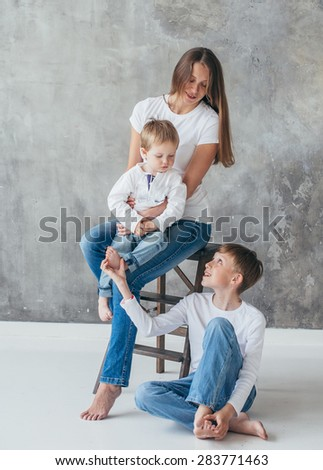 Mother with children sons happy studio portrait full length - stock photo