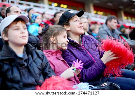 Mother with daughter and son among fans at stadium - stock photo