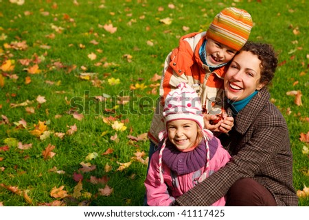 mother with?daughter and?son in sunny autumnal park - stock photo