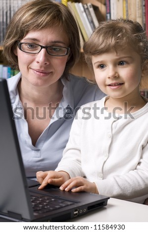 Mother with daughter at computer - stock photo