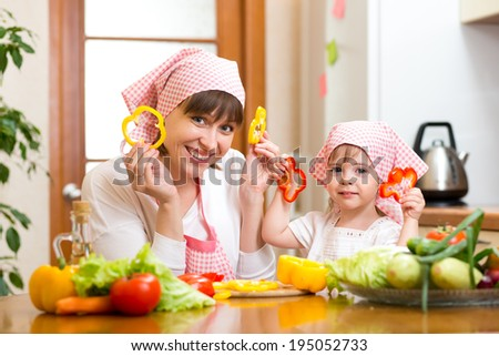 mother with daughter cooking and having fun - stock photo
