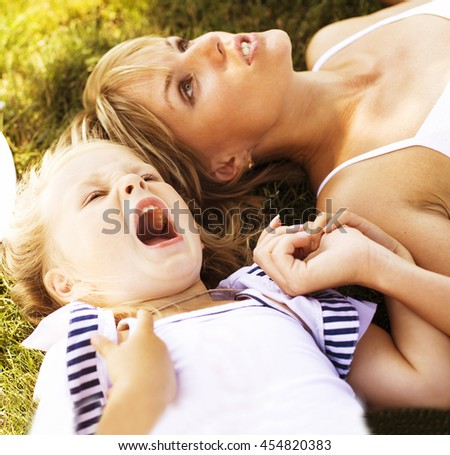 mother with daughter having fun on grass - stock photo