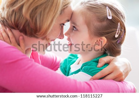 Mother with daughter hugging - stock photo
