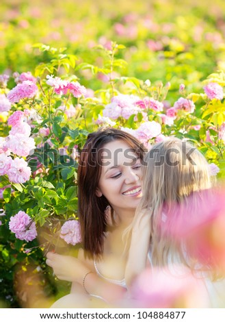 Mother with daughter in rose flowers garden - stock photo