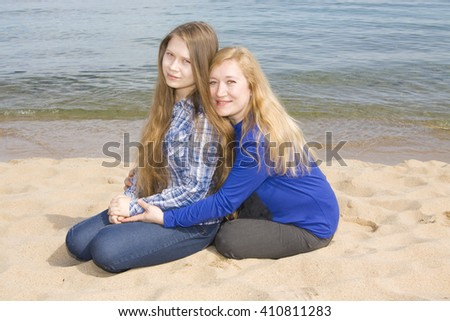 mother with daughter of sixteen years, European, sit on beach near sea. - stock photo