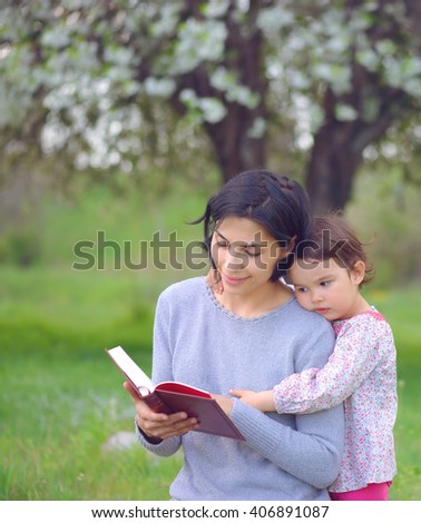 mother with daughter read a book on the meadow - stock photo