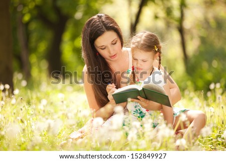 Mother with daughter read the book in the park - stock photo
