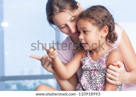 Mother with daughter sitting together and pointing at something - stock photo