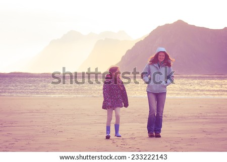 mother with daughter walking by sandy beach at sunset time  - stock photo