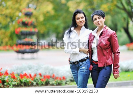 Mother with daughter walking in autumn park - stock photo