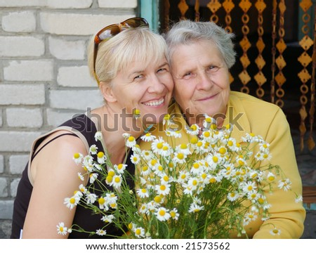 mother with daughter with bouquet camomile - stock photo