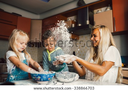 Mother with family haveing fun in the kitchen - stock photo