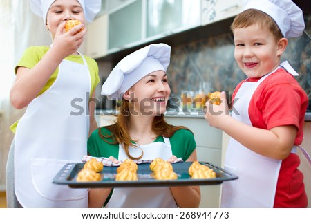 Mother with happy children making bread in the kitchen - stock photo