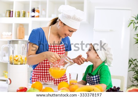 Mother with healthy orange juice and her happy little child in kitchen - stock photo