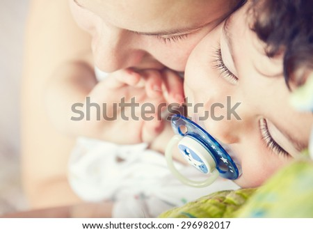 Mother with her adorable baby boy lying on the bed. Toned photo, shallow depth of field. - stock photo