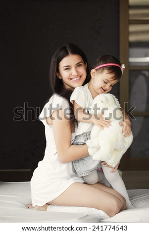 Mother with her baby at home. happy young mother playing with her daughter on the bed at home. happy mother holding her child playing in the room - stock photo
