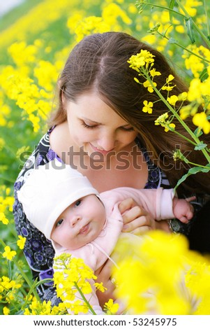 Mother with her baby outdoors in the rapeseed field - stock photo