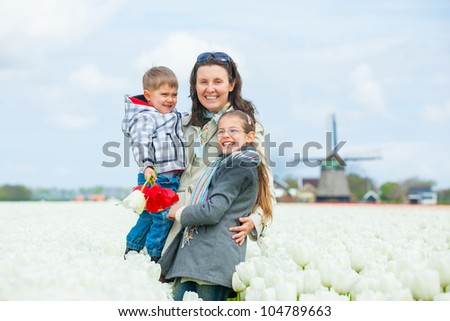 Mother with her child walks between of the white tulips field - stock photo