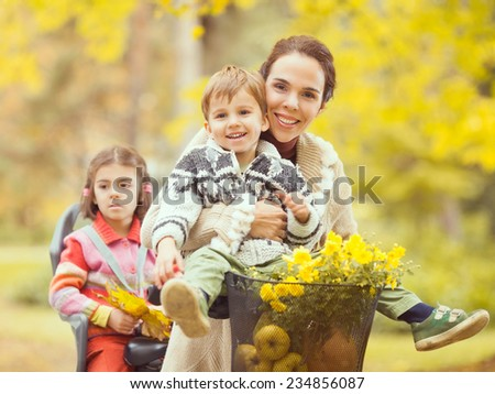 Mother with her cute children on a bike - stock photo