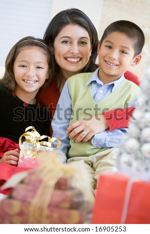 Mother With Her Daughter And Son Holding Christmas Gifts - stock photo