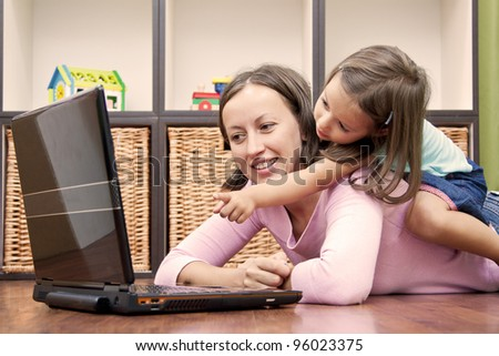 mother with her daughter, internet education - stock photo