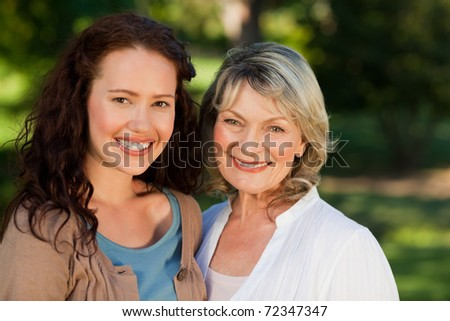 Mother with her daughter looking at the camera in the park - stock photo